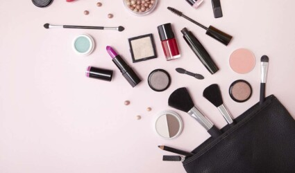 A black make up bag with assorted cosmetic beauty products