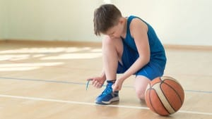 A young basketball player lacing shoes