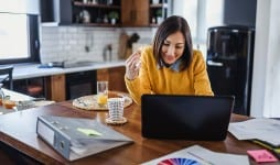 Busy woman eating salad while working on computer