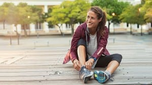 Cheerful runner sitting on floor on city streets with mobile and earphones wearing sport shoes