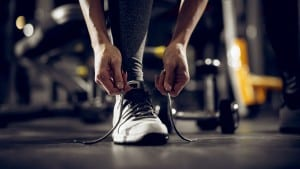 Close up front view of womans hands tying shoelaces on sneakers in the gym