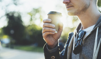 Close up of young man holding coffee to take away at early morning in sunny park sunlight blurred background