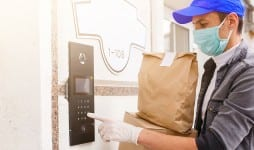 Courier in protective mask and medical gloves delivers takeaway food