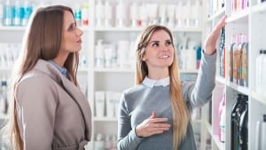 Customer woman choosing cosmetics with assistant at beauty store