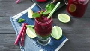 Glass of mixed vegetable smoothie on wooden table