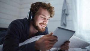Happy guy with tablet watching movie in bed