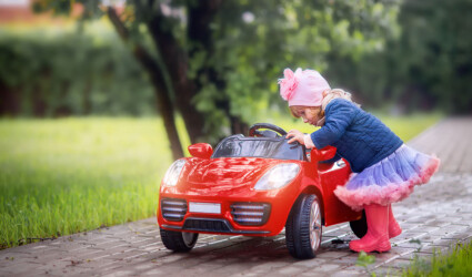 Little girl with toy red car cabriolet