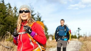 Man and woman hikers hiking on mountain trail autumn or winter nature