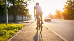 Man is riding the bike by road