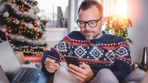 Man wearing blue sweater shopping online and using credit card
