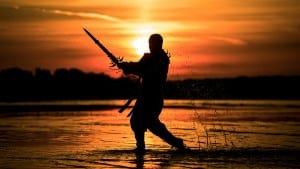 Silhouette of assassin with the sword at the beach