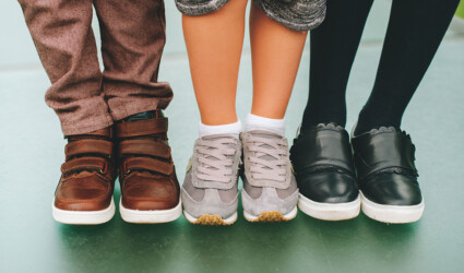 Three pairs of childrens feet wearing comfortable and fashion trainers