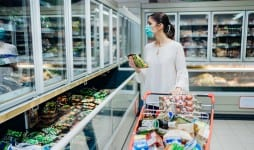 Woman wearing face mask buying in supermarket
