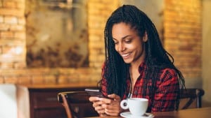 Young african woman at cafe drinking coffee and using mobile phone