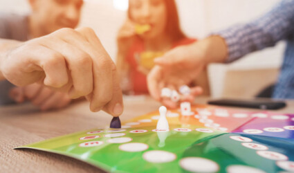Young people play a board game using a dice and chips