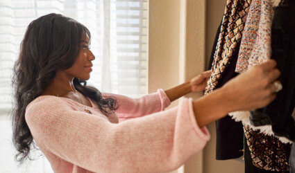 african american woman looking through closet