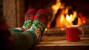 feet woollen socks by christmas fireplace