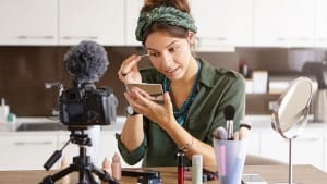 female blogger does make up reviews beauty product for video blog