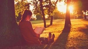 girl reading book park summer sunset