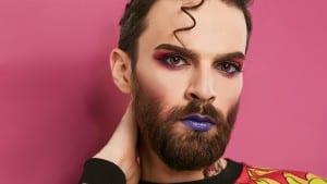 guy wearing hipster beard purple lipstick pink eyeshadow curly hairstyle