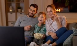 happy smiling father mother and little son eating popcorn and watching tv at home in evening