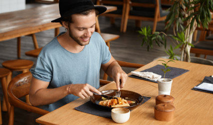 man enjoying lunch sitting at wooden table alone