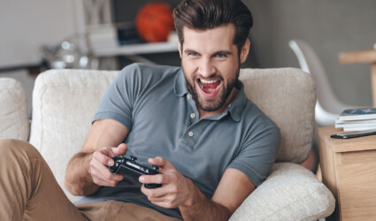 man playing video game and keeping mouth open while sitting on the couch at home