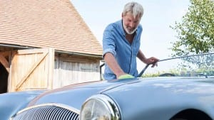 mature man polishing restored classic sports