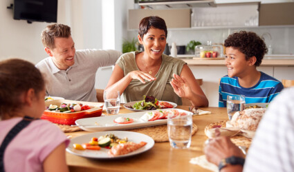 multigeneration mixed race family eating meal