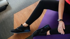 op view of legs of young sportswoman with fitness tracker on hand in black leggings sitting on the floor in gym