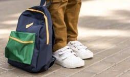 stylish schoolboy standing backpack