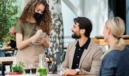 waitress face mask serving happy couple
