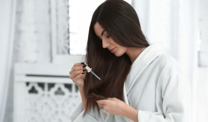 woman applying serum onto her long hair at home