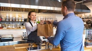 woman giving bag with takeaway food to client