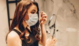 woman medical mask black dress applying