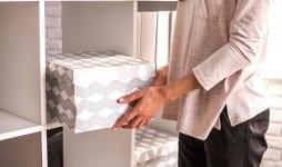 woman put cardboard box on shelf