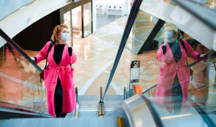 woman rides escalator shopping protective mask on face