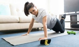 woman watching online workout tutorials over her phone at home