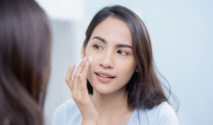 women applying face lotion