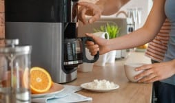 young couple using coffee machine kitchen