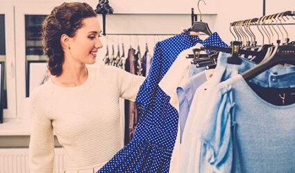 young woman choosing clothes on rack